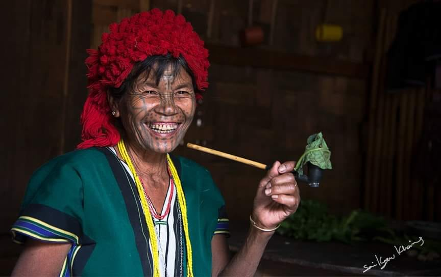 A tattooed woman on her way to the coffee plantations in Chin State