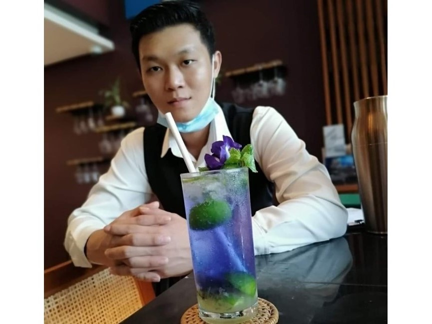 Alexander, bartender with a blue Mojito in Yangon. You, too, can be creative and make your own drink!