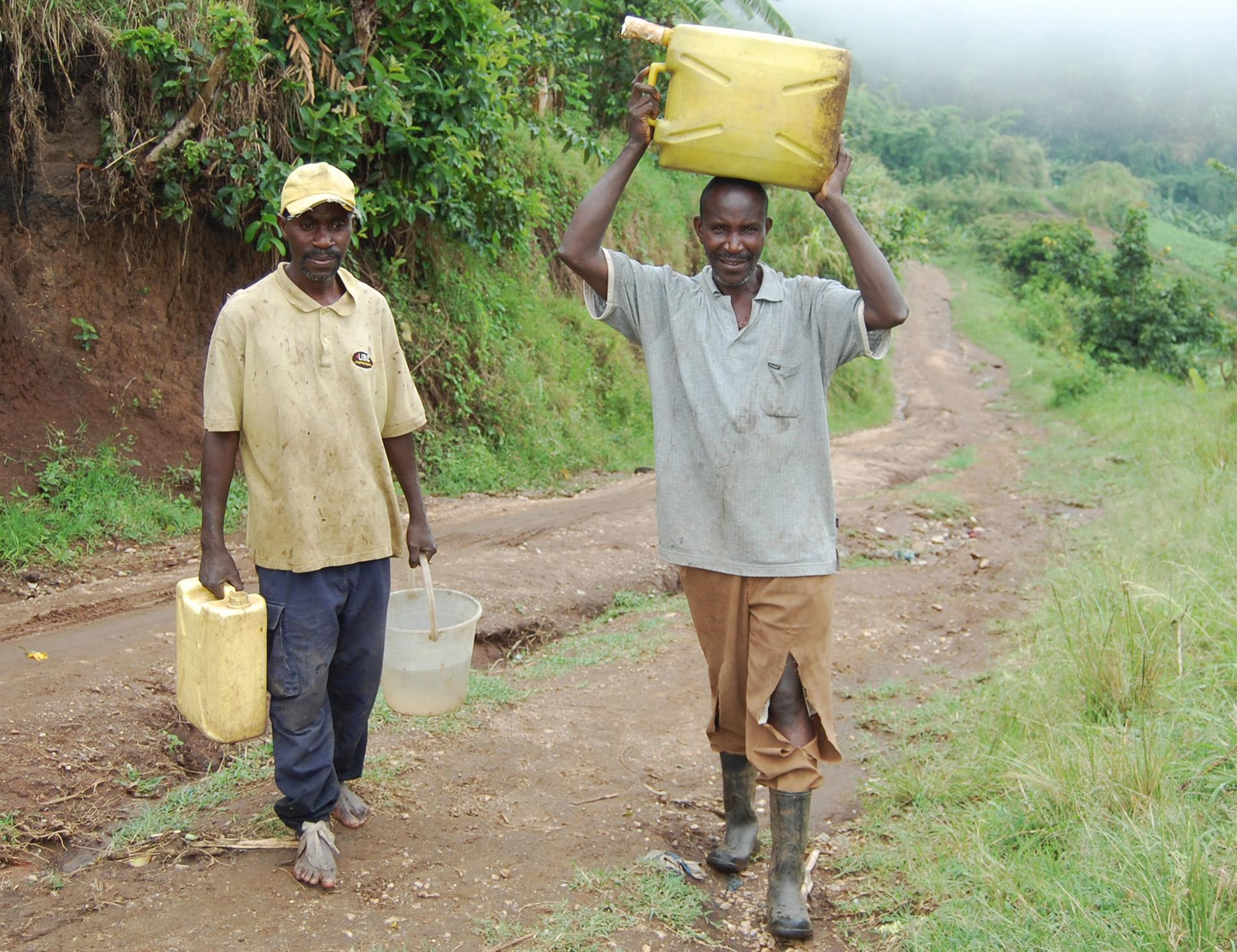 Pius Masereka und Exavier Bwanandeke tragen die Wasserkanister zur Waschstation (v.l.n.r.)